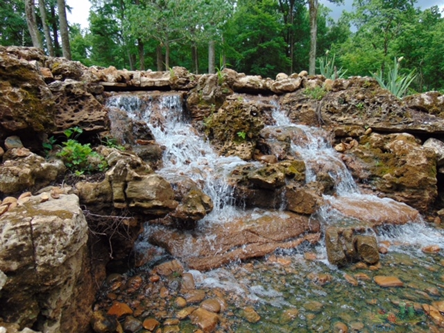 Beautiful large pondless waterfall created using weathered limestone boulders and ledge rock.
